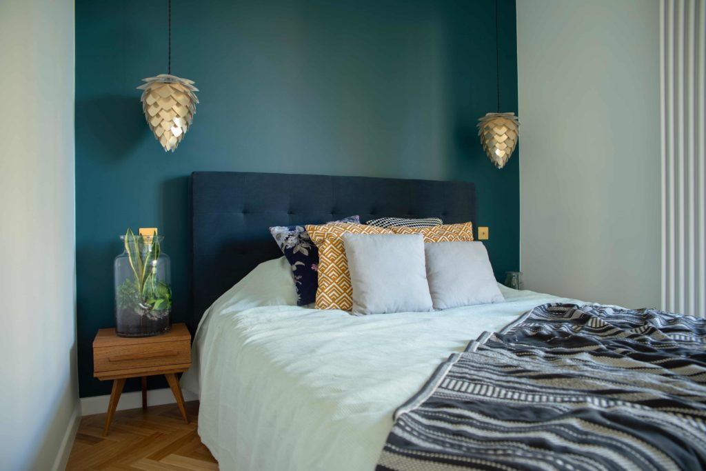 Blue feature wall in a bedroom with statement bed