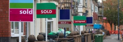 estate agent for sale signs down a uk residential street